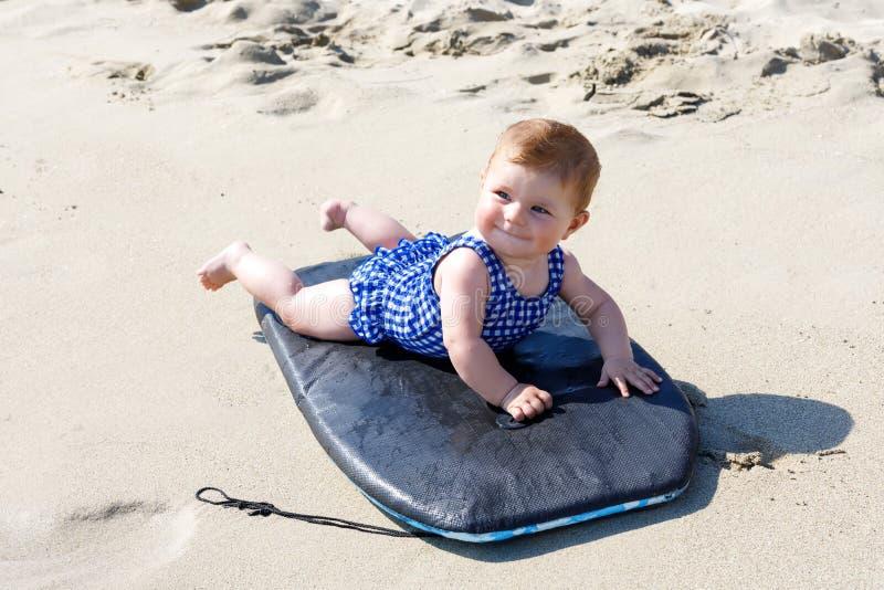 Portret śliczna mała dziewczynka w pływanie kostiumu na plaży w lecie Uroczy dziecko ma zabawę na kipieli desce dziecko moda fotografia stock