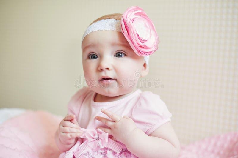 Portret śliczna mała dziewczynka z menchiami kłania się kwiatu na jej głowie obraz royalty free