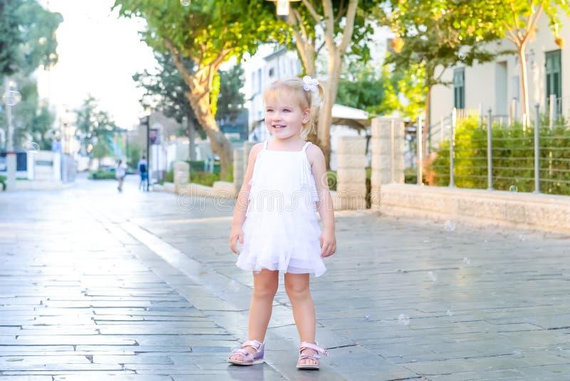Portret śliczna mała emocjonalna blondy berbeć dziewczyna w bielu bawić się i łapie smokingowych mydlanych bąblach podczas spacer obraz stock