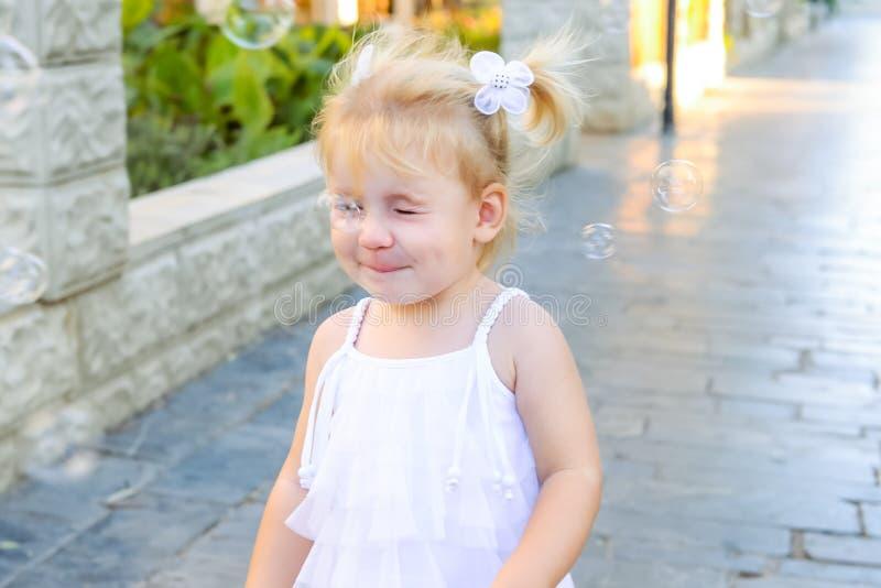 Portret śliczna mała emocjonalna blondy berbeć dziewczyna w sukni z mydlanych bąbli łamać jej nos Spacer w miasto parku acti zdjęcie royalty free