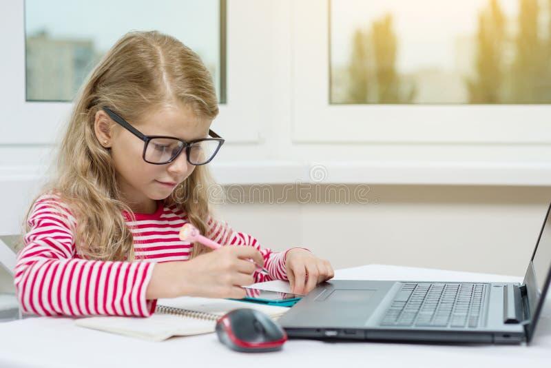 Portret śliczna 7 roczniaka dziewczyna jest ubranym szkła, używać laptop, obrazy stock