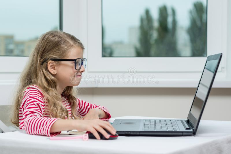 Portret śliczna 7 roczniaka dziewczyna jest ubranym szkła, używać laptop, smartphone i pisać w notepad obsiadaniu, przy stołem zdjęcie stock