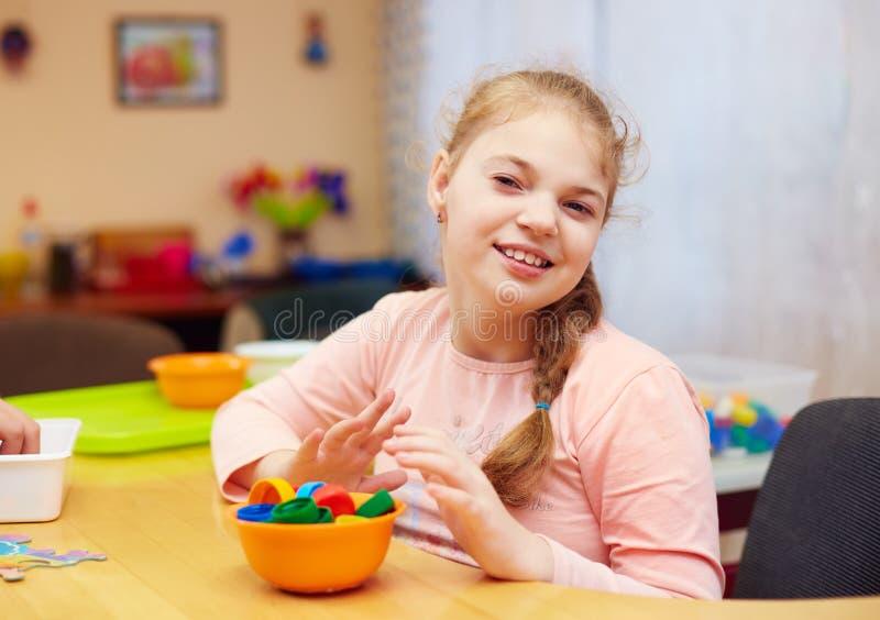 Portret śliczna szczęśliwa dziewczyna z kalectwem rozwija świetne motorowe umiejętności przy centrum rehabilitacji dla dzieciaków obraz stock
