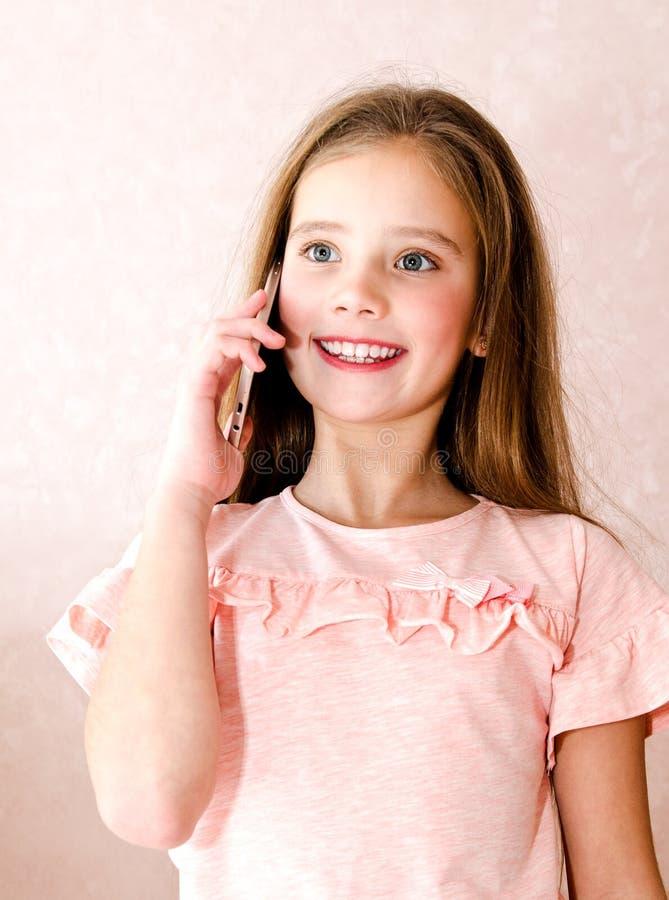 Portret śliczna uśmiechnięta mała dziewczynka dzwoni telefonem komórkowym smar fotografia stock
