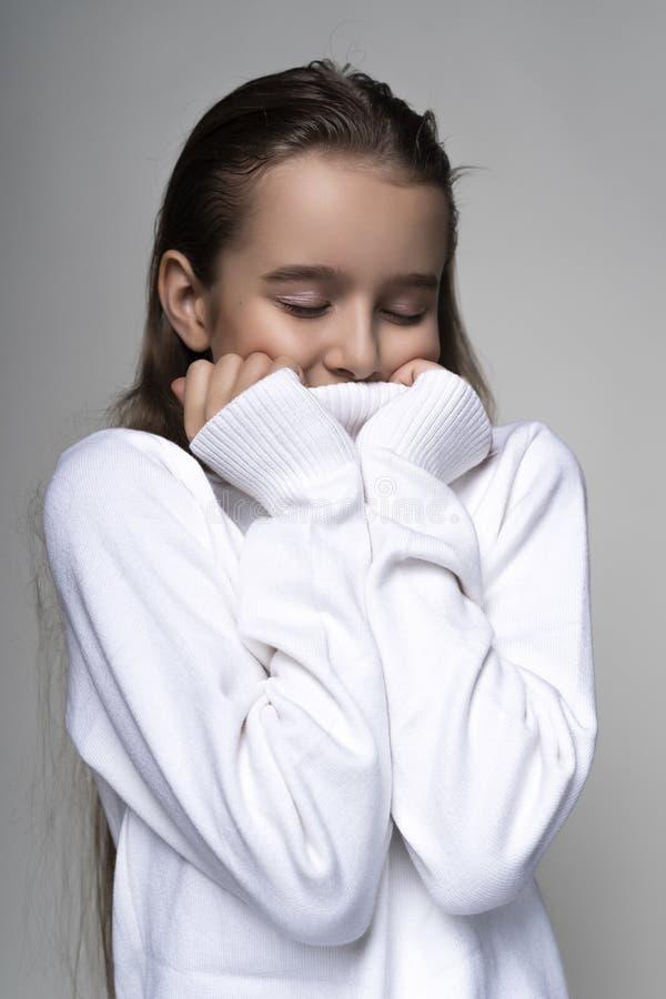 Portret śliczna uśmiechnięta nastoletnia dziewczyna jest ubranym białego turtleneck pulower Odizolowywający na szarym tle Reklamo zdjęcie royalty free