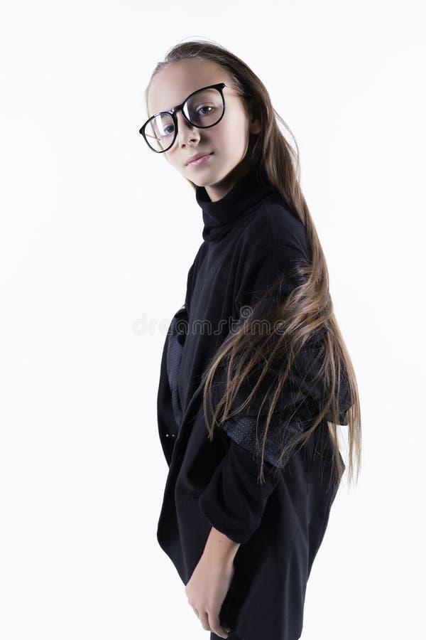 Portret śliczna uśmiechnięta nastoletnia dziewczyna jest ubranym turtleneck, kurtka blezer i eyeglasses ciemnych, pojedynczy bia? fotografia stock