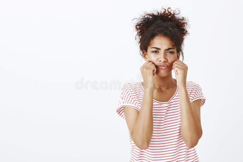 Portret ślicznego dąsania afroamerykańska kobieta z rozczesanym kędzierzawym włosy, ciągnięcie policzki z rękami i marszczyć brwi zdjęcie stock
