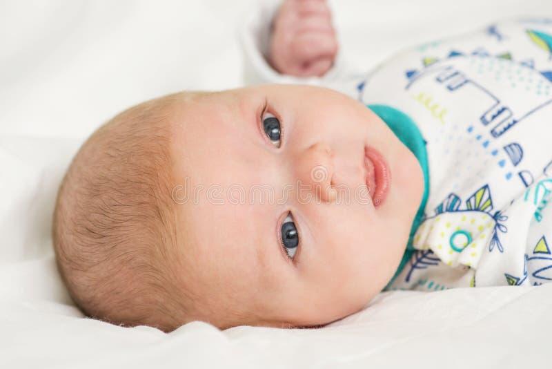 Portret ślicznego dziecka łgarski puszek na łóżku Nowy rodziny i mi?o?ci poj?cie Szczęśliwy berbeć w bodysuit obrazy stock