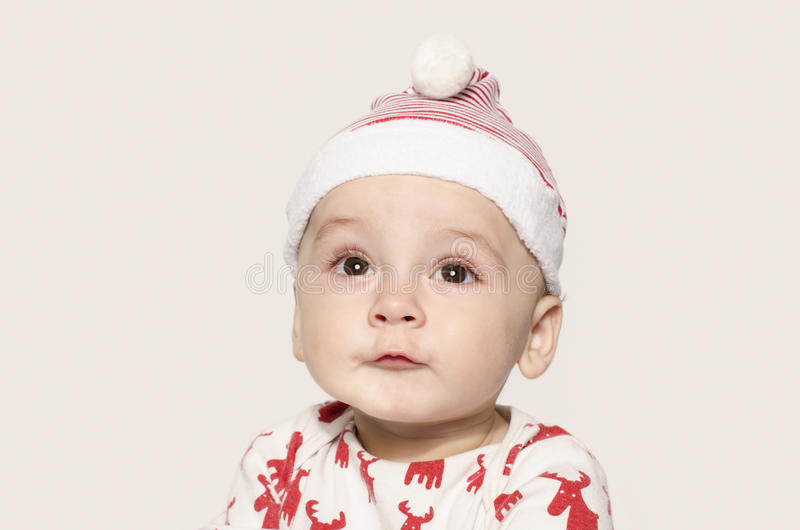 Portret ślicznej chłopiec przyglądający up główkowanie jest ubranym Santa kapelusz fotografia stock