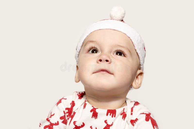 Portret ślicznej chłopiec przyglądający up główkowanie jest ubranym Santa kapelusz zdjęcie stock