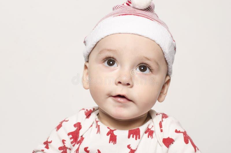 Portret ślicznej chłopiec przyglądający up główkowanie jest ubranym Santa kapelusz obrazy royalty free