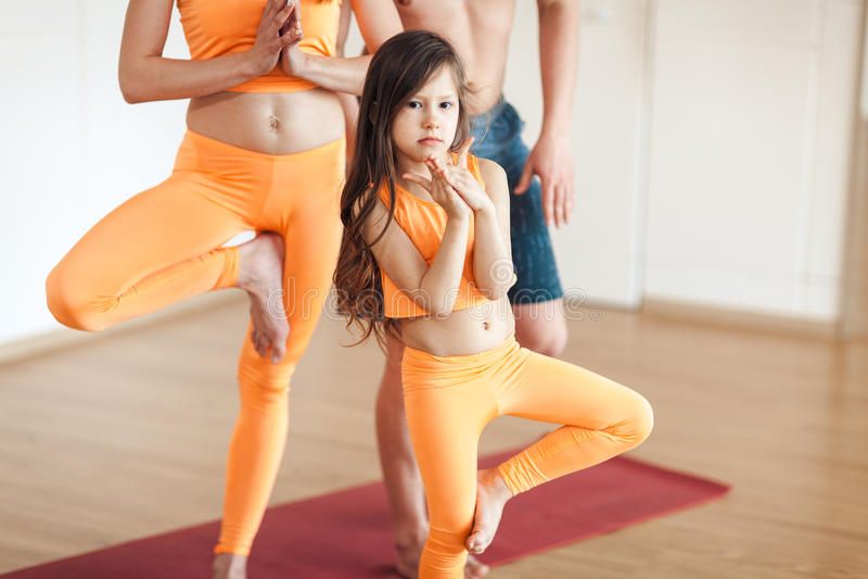 Portret ślicznej małej uśmiechniętej dziewczyny ćwiczy joga w pomarańczowym kostiumu, robi joga fotografia stock