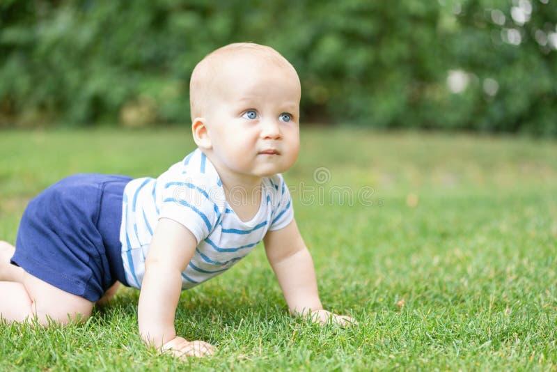 Portret śliczny blond zadumany chłopiec czołganie na zielonej trawy gazonie outdoors Rozważny dzieciak myśleć o coś Pytanie o fotografia royalty free