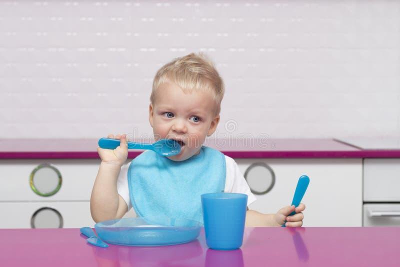 Portret śliczny blondynka berbeć w błękitnym śliniaczku z rozwidleniem i nożu w jego rękach W Wysokim krześle w nowożytny kuchenn fotografia stock