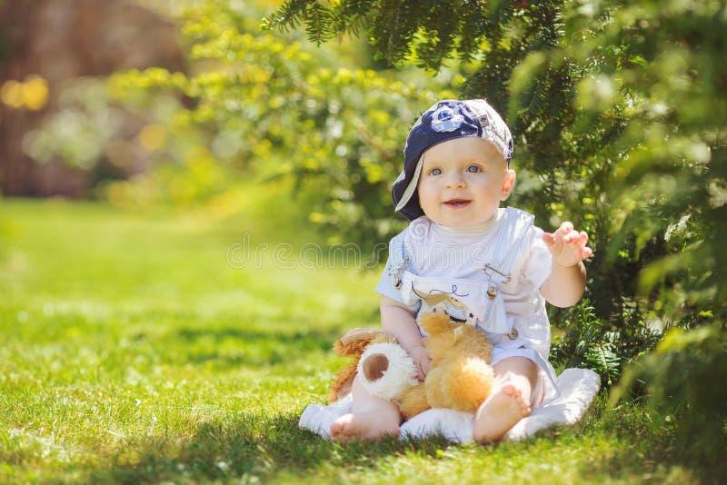 Portret śliczny chłopiec obsiadanie na trawie fotografia stock