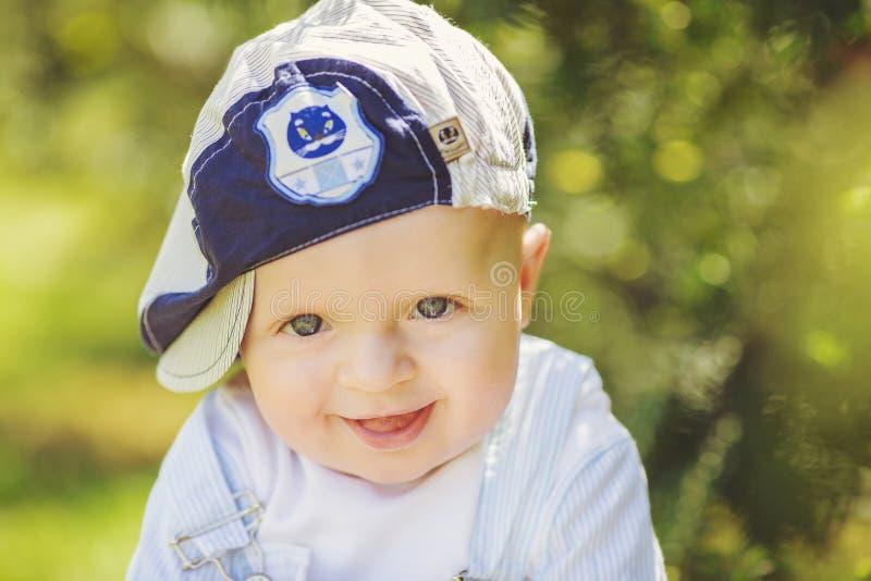 Portret śliczny chłopiec obsiadanie na trawie zdjęcia stock