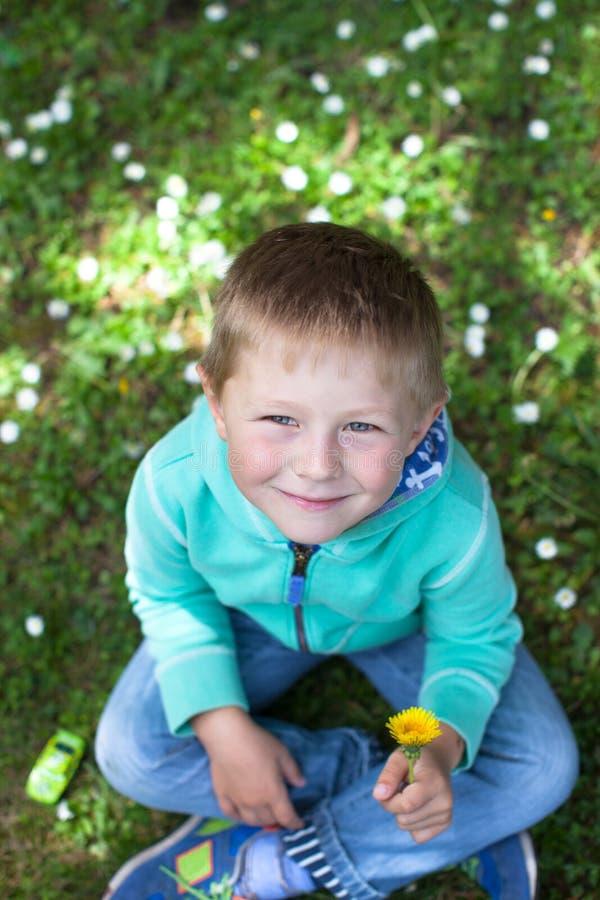 Portret śliczny chłopiec obsiadanie na trawie obrazy royalty free