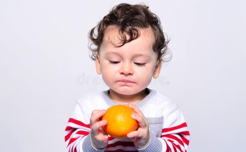 Portret śliczny dziecko czuje zażenowanie przy pomarańcze obraz royalty free