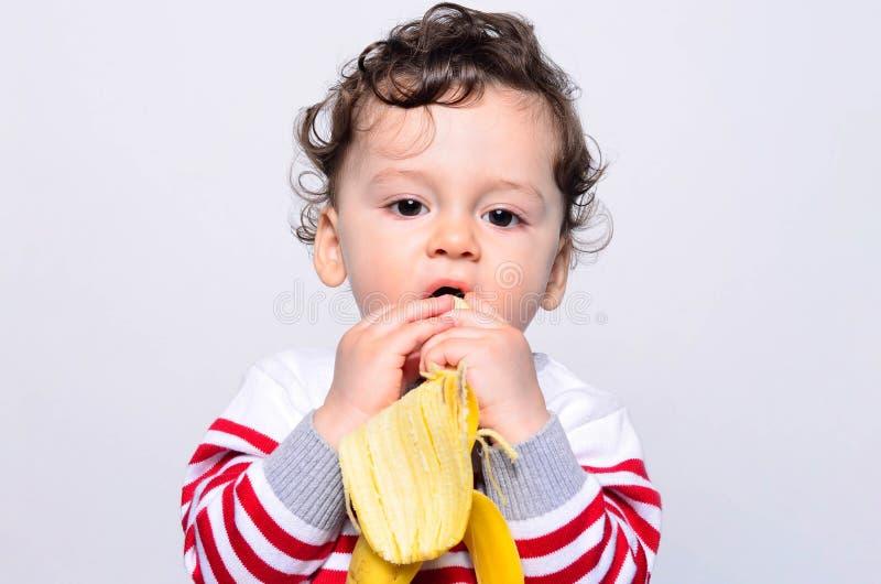 Portret śliczny dziecko je banana zdjęcie royalty free