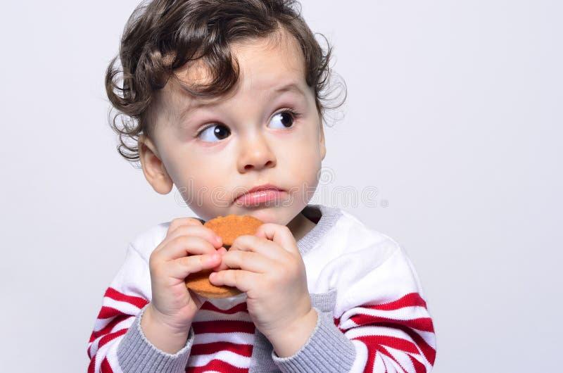 Portret śliczny dziecko je biskwitowy przyglądający up ciekawego obraz stock