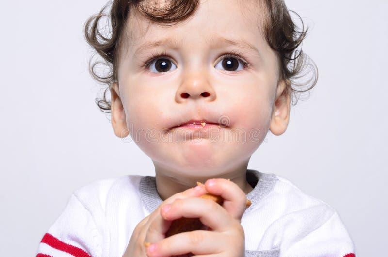 Portret śliczny dziecko je ciastko robi śmiesznej twarzy fotografia royalty free