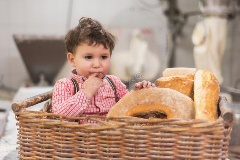 Portret śliczny dziecko wśrodku kosza z chlebem w piekarni zdjęcie royalty free