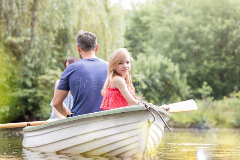 Portret śliczny dziewczyny obsiadanie z ojcem na rowboat w jeziorze podczas lata fotografia stock
