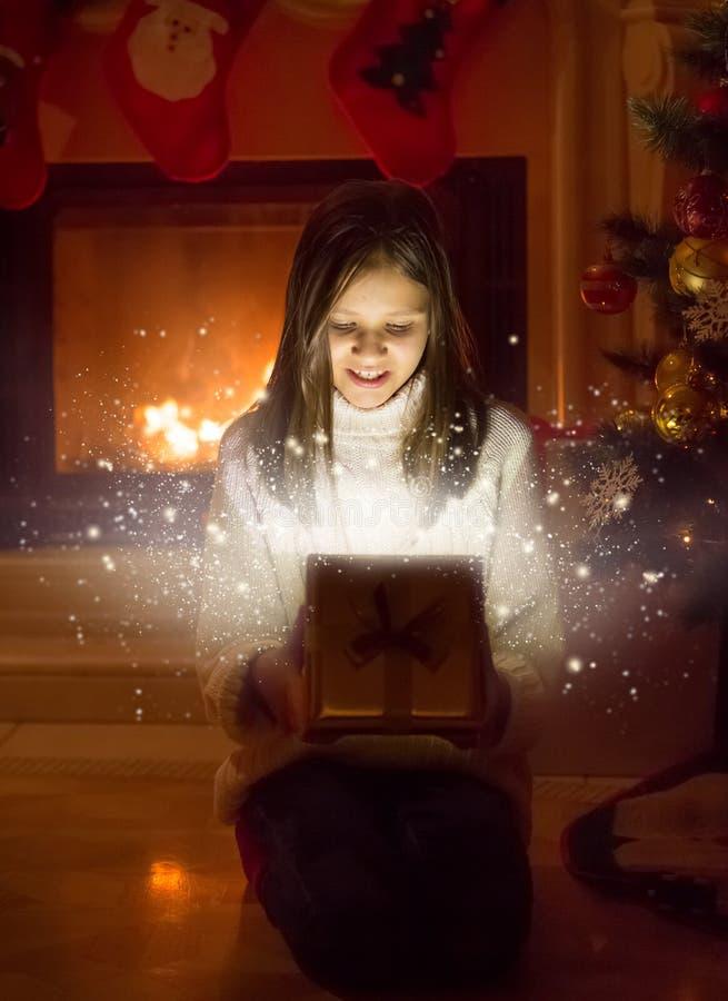 Portret śliczny dziewczyny otwarcia pudełko z Bożenarodzeniową teraźniejszością światło zdjęcia stock