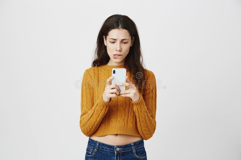 Portret śliczny europejski dziewczyny mienia smartphone i patrzeć ekran niespokojny i intrygujący podczas gdy gryźć wargę i być obraz royalty free