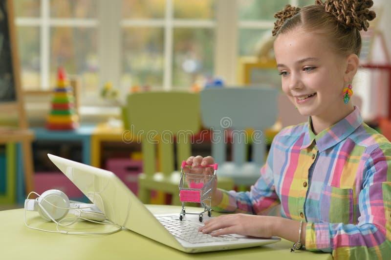 Portret śliczny małej dziewczynki obsiadanie przy stołem z laptopu i mienia małym wózkiem na zakupy, online zakupy pojęcie fotografia stock