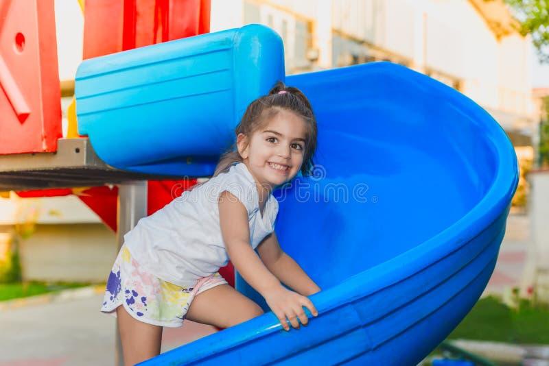 Portret śliczny małej dziewczynki pięcie na suwakach zdjęcie stock