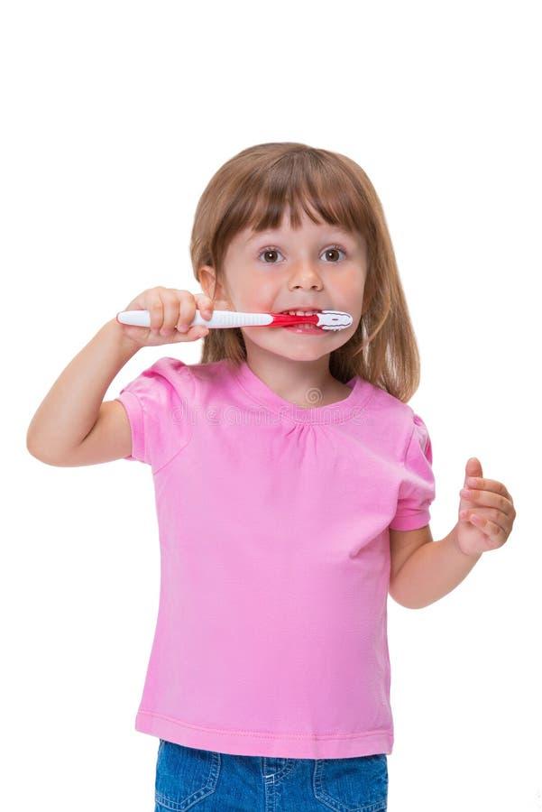 Portret śliczny małej dziewczynki 3 roczniak w różowej koszulce szczotkuje jej zęby odizolowywających na białym tle fotografia stock