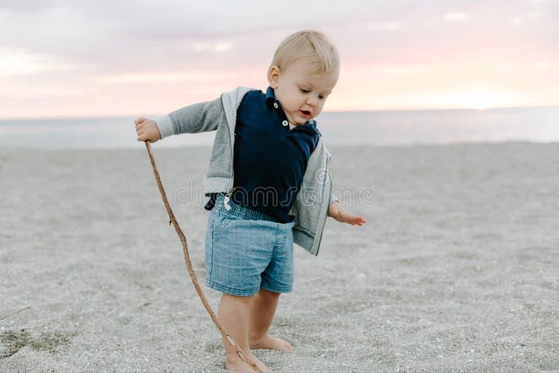 Portret Śliczny Mały chłopiec dziecko Bawić się i Bada w piasku przy plażą Podczas zmierzchu Outside na wakacje w Hoodie obraz royalty free
