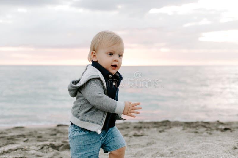 Portret Śliczny Mały chłopiec dziecko Bawić się i Bada w piasku przy plażą Podczas zmierzchu Outside na wakacje w Hoodie zdjęcie royalty free
