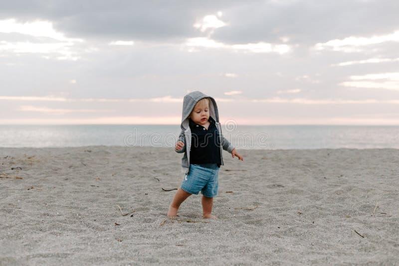 Portret Śliczny Mały chłopiec dziecko Bawić się i Bada w piasku przy plażą Podczas zmierzchu Outside na wakacje w Hoodie zdjęcia stock