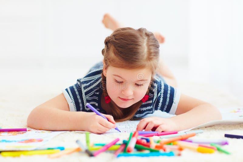 Portret śliczny szczęśliwy dziewczyna rysunek, podczas gdy kłaść na dywanie obrazy stock