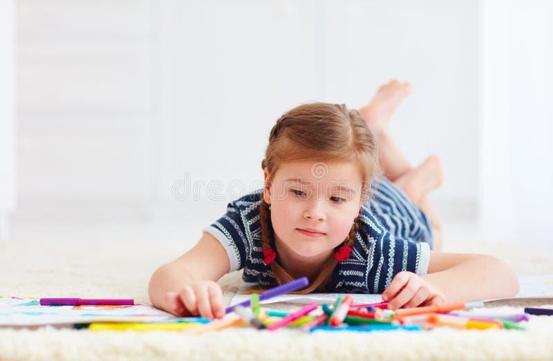 Portret śliczny szczęśliwy dziewczyna rysunek, podczas gdy kłaść na dywanie zdjęcie royalty free
