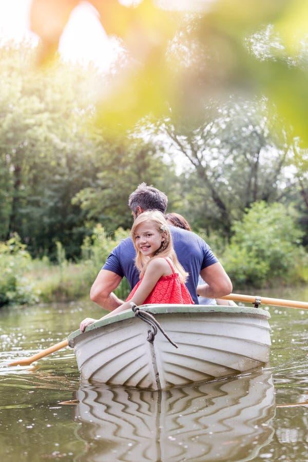 Portret śliczny uśmiechnięty dziewczyny obsiadanie z ojcem na rowboat w jeziorze podczas lata obraz royalty free