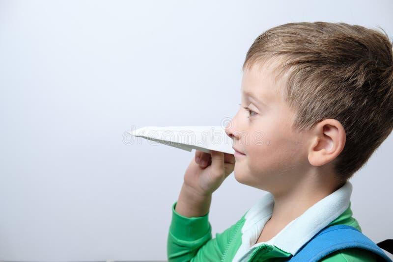Portret śliczny uczeń z błękitnym plecaka i papieru airpla obrazy royalty free