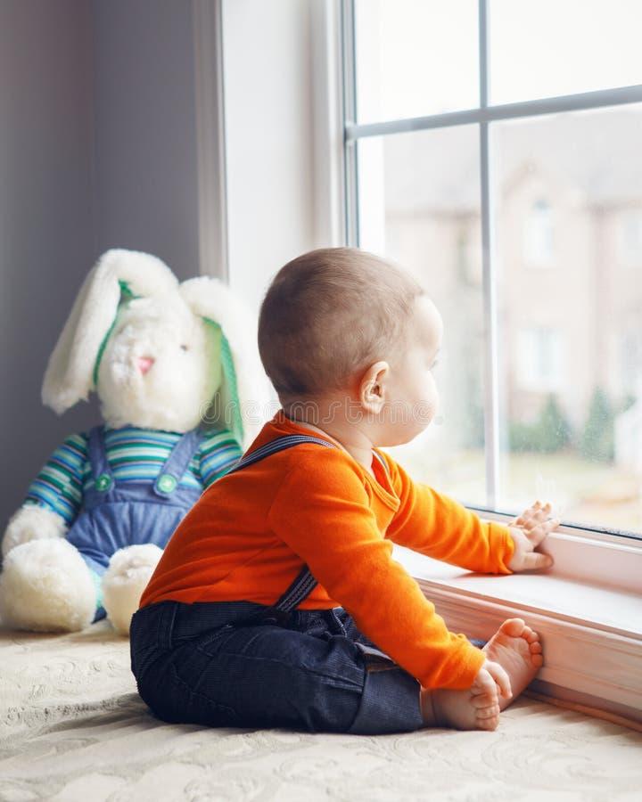 Portret śliczny uroczy Kaukaski chłopiec obsiadanie na windowsi fotografia stock