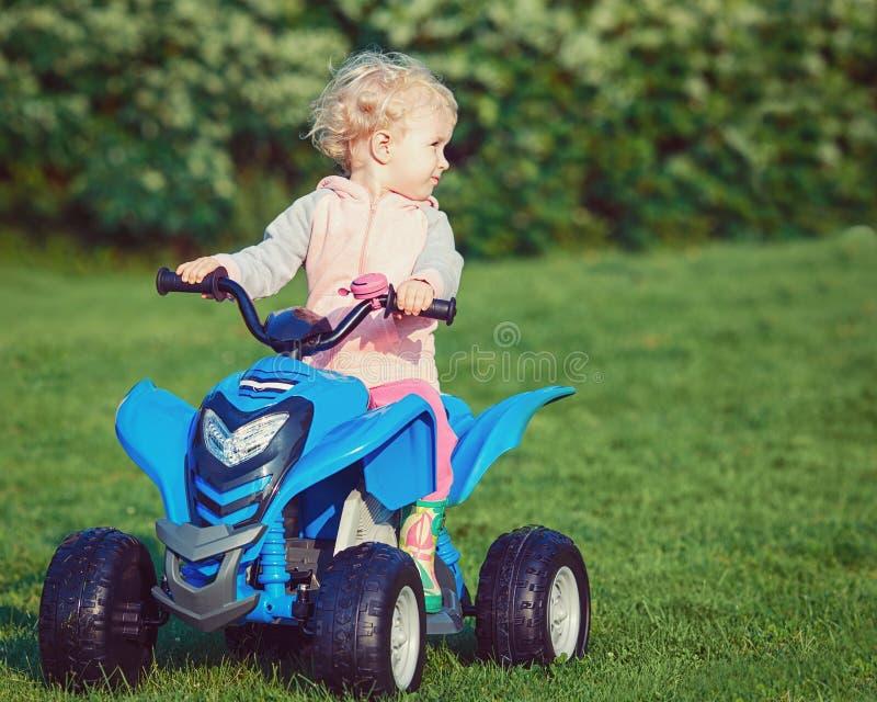 Portret śliczny uroczy szczęśliwy mały blond Kaukaski chłopiec dziewczyny dziecko jedzie błękitnego elektrycznego samochód w park obraz royalty free