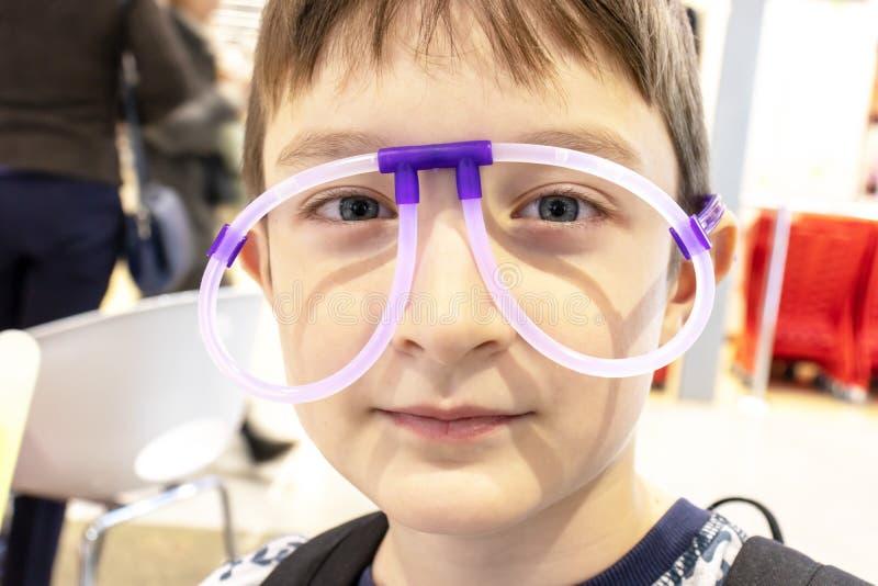 Portret śmieszna śliczna chłopiec jest ubranym dziwacznych szkła robić fluorescencyjne neonowe tubki, centrum handlowe fotografia stock