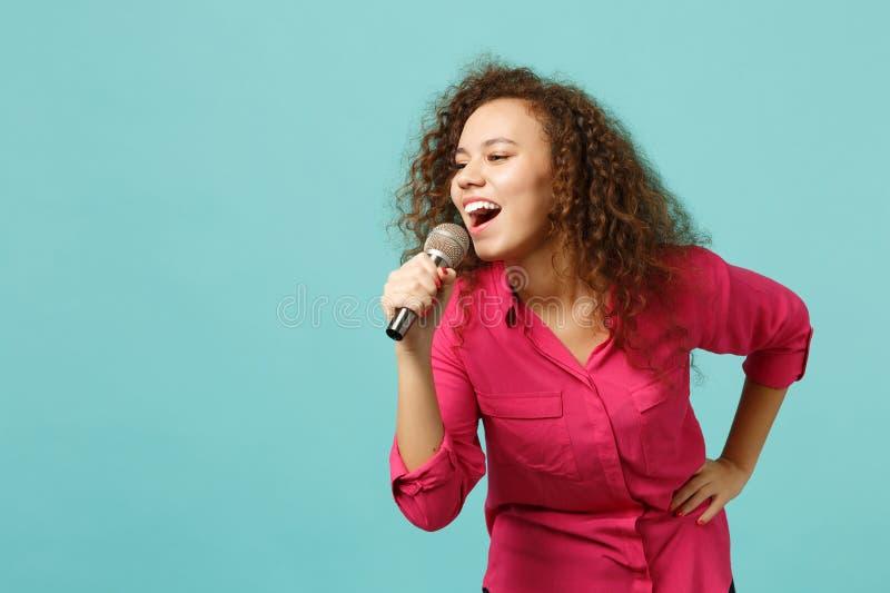 Portret śmieszna afrykańska dziewczyna tanczy w przypadkowych ubraniach, śpiewa piosenkę w mikrofonie odizolowywającym na błękitn zdjęcie royalty free