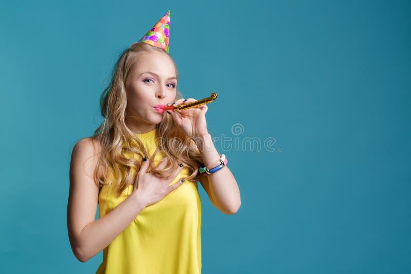 Portret śmieszna blond kobieta w urodzinowym kapeluszu i kolor żółty koszula na błękitnym tle Świętowanie i przyjęcie zdjęcie royalty free