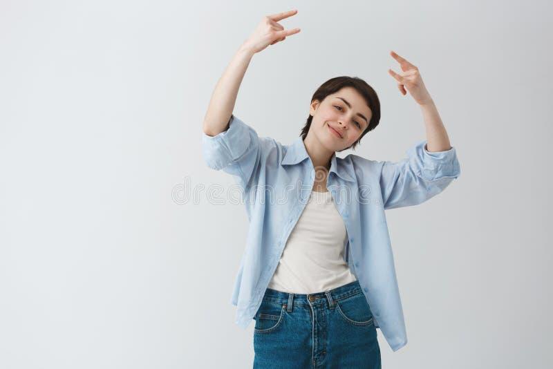 Portret śmieszna młoda studencka dziewczyna gestykuluje i robi rogom z krótkim ciemnym włosy podpisuje z rękami, niemądry pozować fotografia royalty free