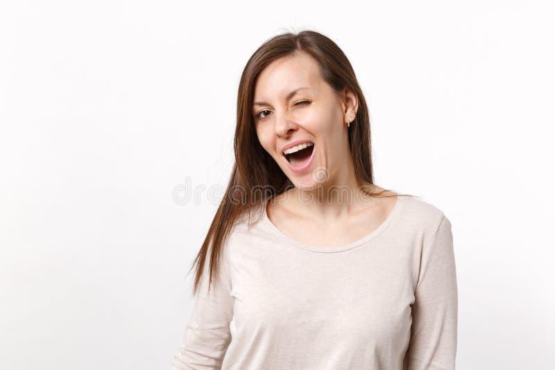 Portret śmieszna rozochocona uśmiechnięta mruganie brunetki młoda kobieta w światło odzieżowej pozycji odizolowywającej na białym fotografia stock