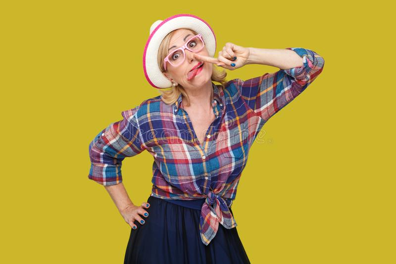Portret śmieszna szalona nowożytna elegancka dojrzała kobieta stoi z palcowym musztrowanie nosem w przypadkowym stylu z kapelusze obrazy stock
