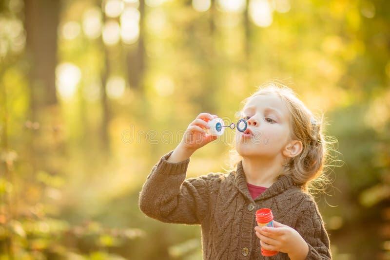Portret śmieszna urocza mała dziewczynka dmucha mydlanych bąble Ślicznej blondynki błękitnooka dziewczyna w kolorze żółtym dział  zdjęcia stock