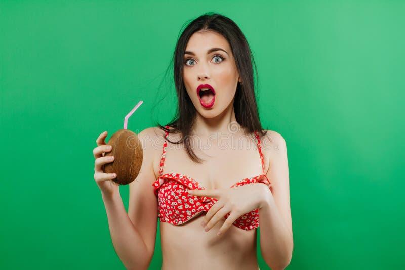 Portret Śmieszna Zdziwiona brunetka w Jaskrawym Swimwear z Tropikalnym koktajlem w rękach na Zielonym tle fotografia royalty free