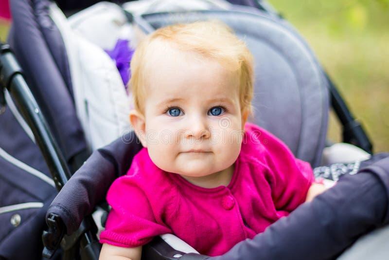 Portret śmieszni dziecko dziewczyny blondyny z niebieskimi oczami siedzi w wózku spacerowym w lecie dla zieleni troszkę Trinaspor obrazy stock